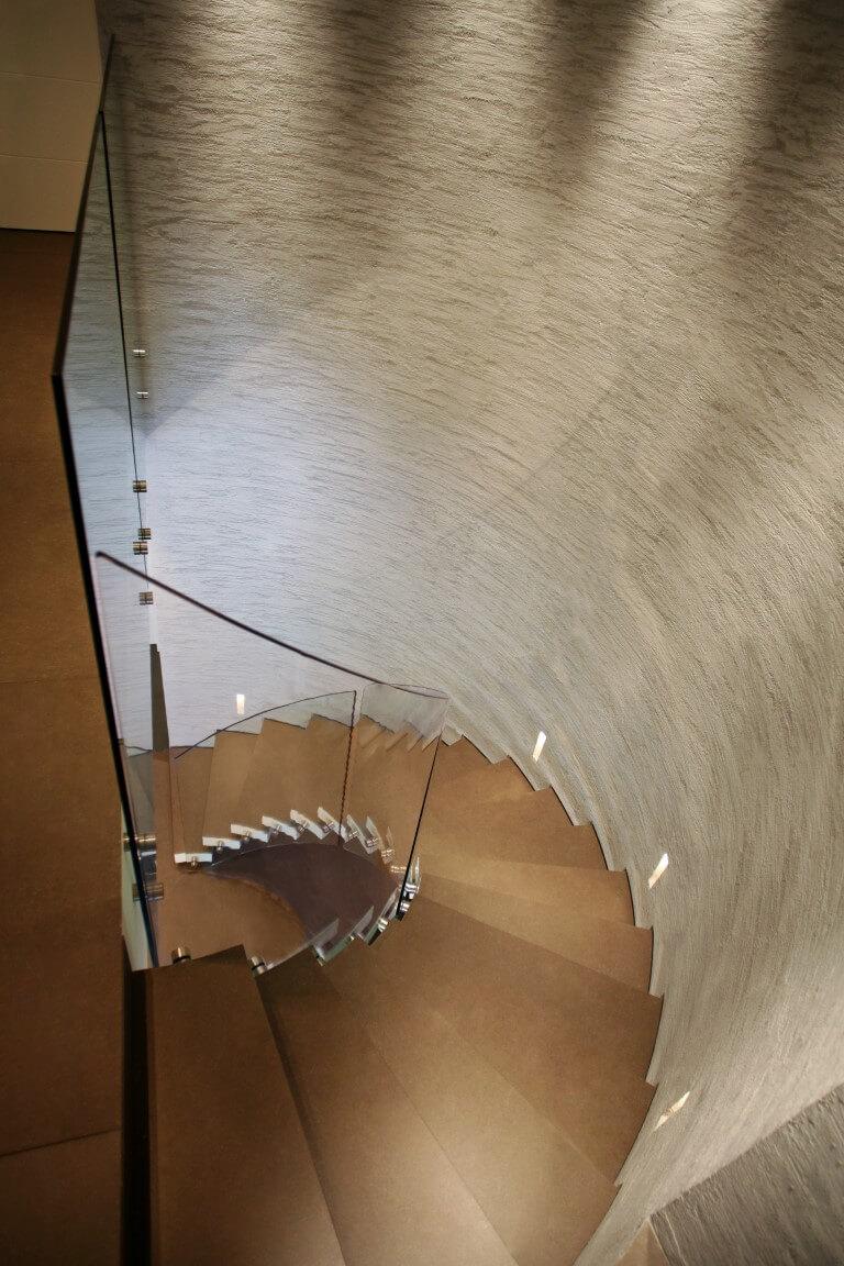 מבט מלמעלה על מדרגות ספירליות מקוריאן בגוונים של עץ עם מעקה זכוכית שקופה
