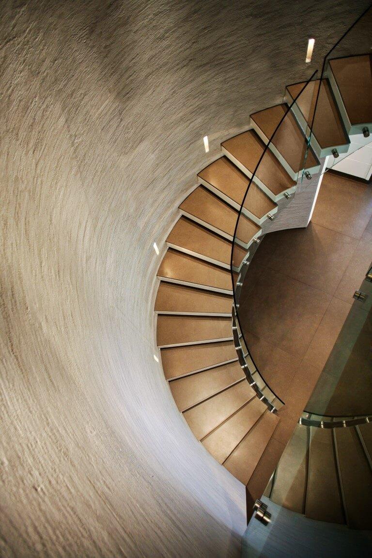 מבט מהקומה השניה אל רצפת הפרקט והמדרגות הלולייניות שעולות מהקומה הראשונה