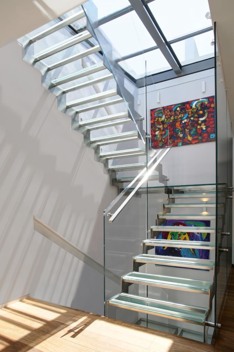 שני גרמי מדרגות נירוסטה וזכוכית עולים אל המפלס העליון מתחת לחלון התקרה העצום