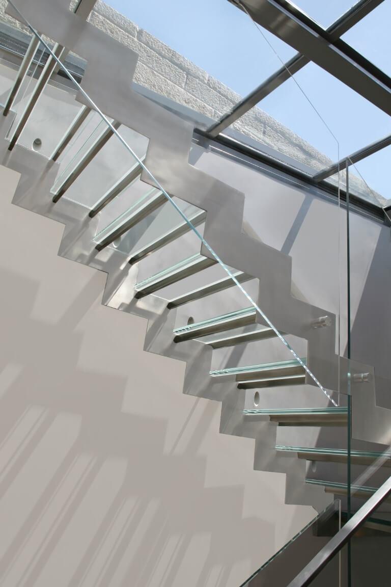 מבט על מדרגות הנירוסטה עם מדרכי הזכוכית מבעד למעקה הזכוכית השקופה