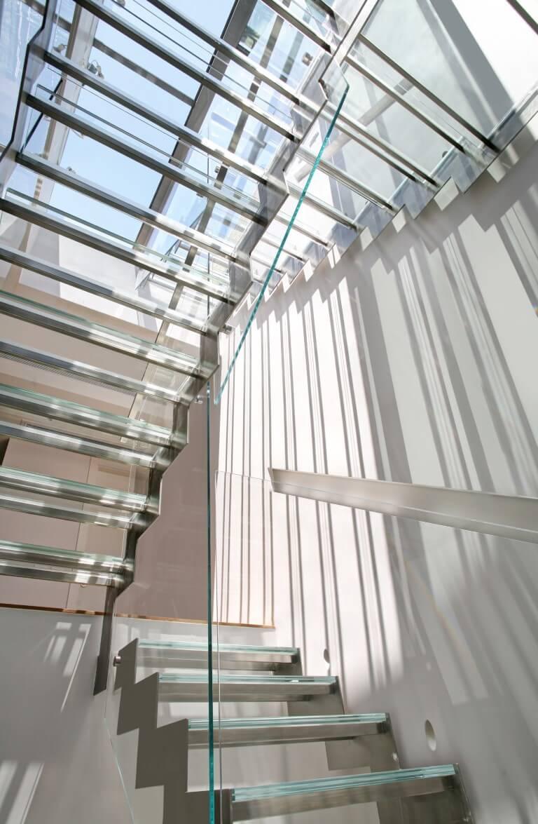 מבט החוצה מהמפלס התחתון דרך גרם מדרגות הזכוכית והחלון בתקרה שמאפשרים לאור לעבור בקלות