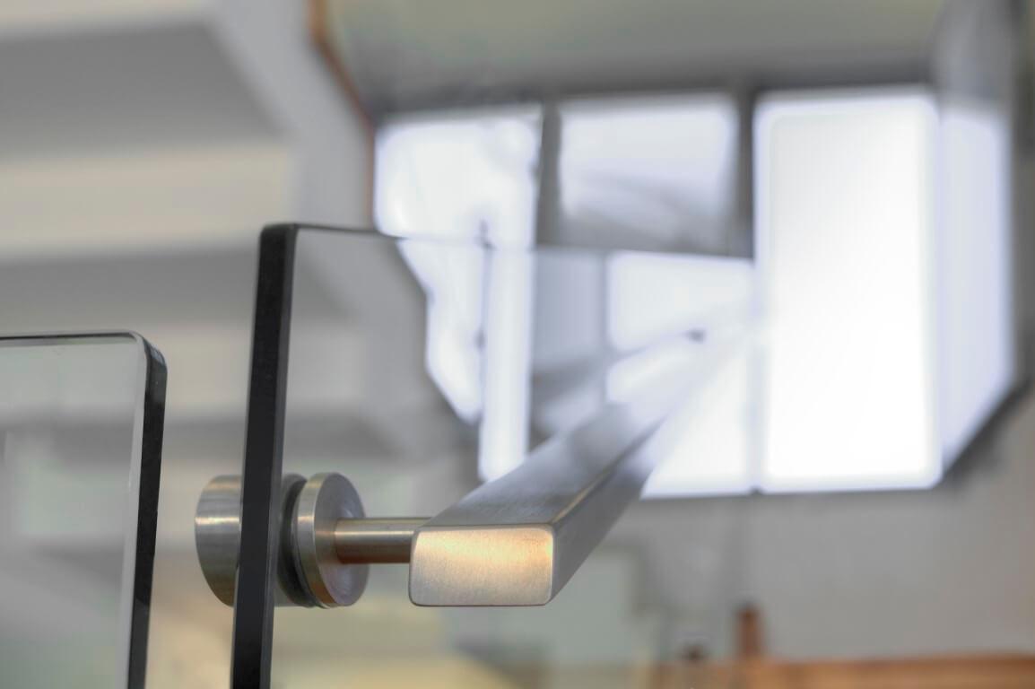 פוקוס על מעקה הזכוכית ומאחז היד מנירוסטה בגימור מושלם