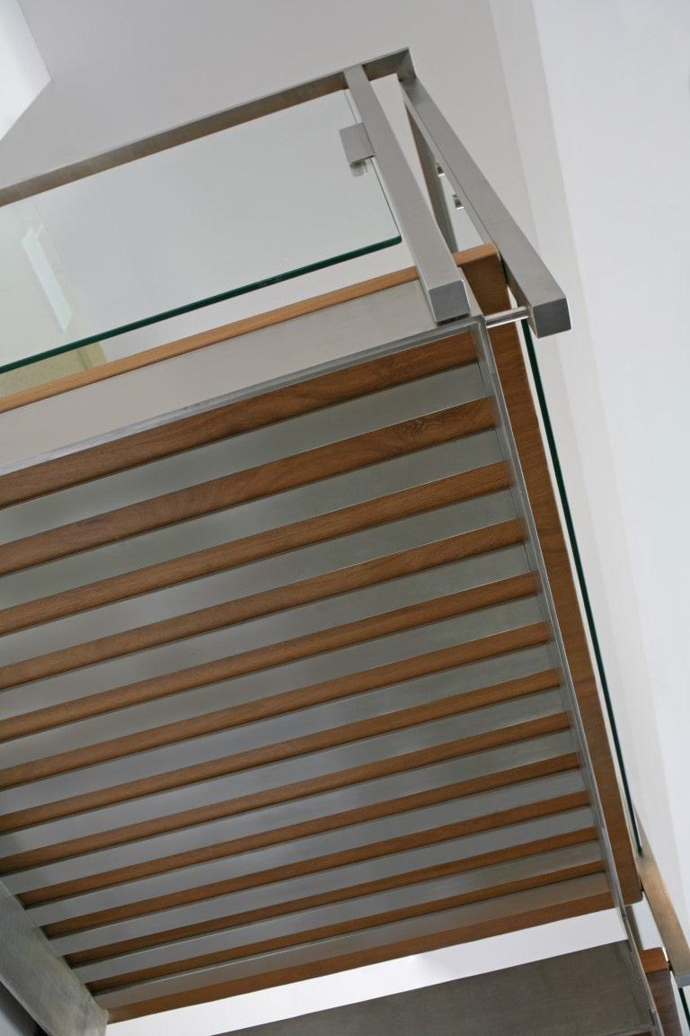 מבט מלמטה על פלטפורמה עליונה של קונסטרוקצית המדרגות שעשויה משילוב של נירוסטה ועץ ומוקפת מעקה זכוכית