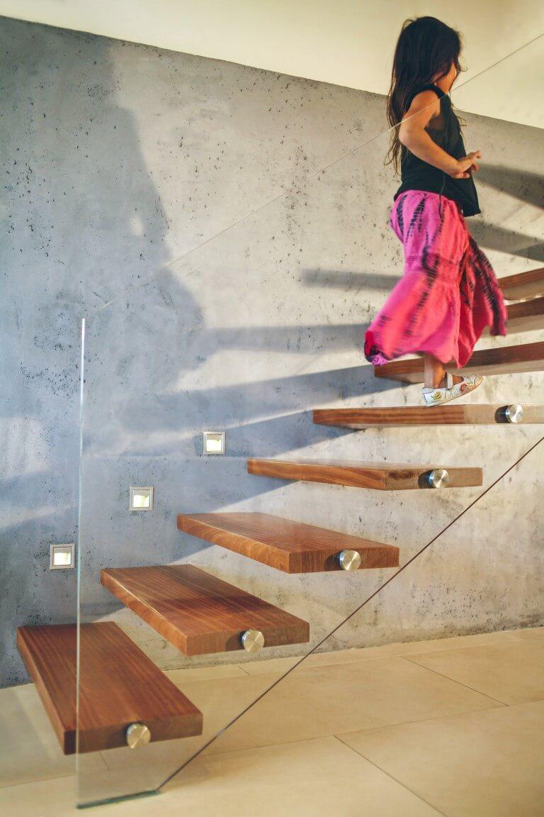 במעלה מדרגות העץ המרחפות לאורך קיר באפור