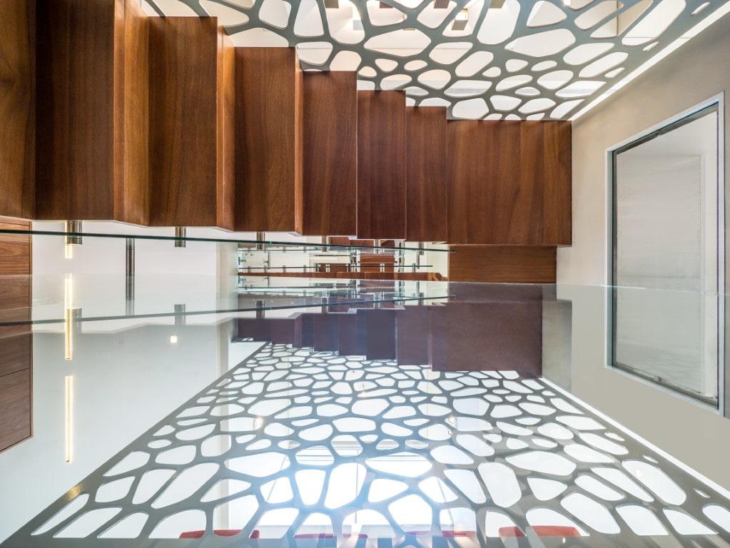מדרגות עץ צפות בגוונים כההים עם מעקה זכוכית מוקפות במחיצות דקורטיביות
