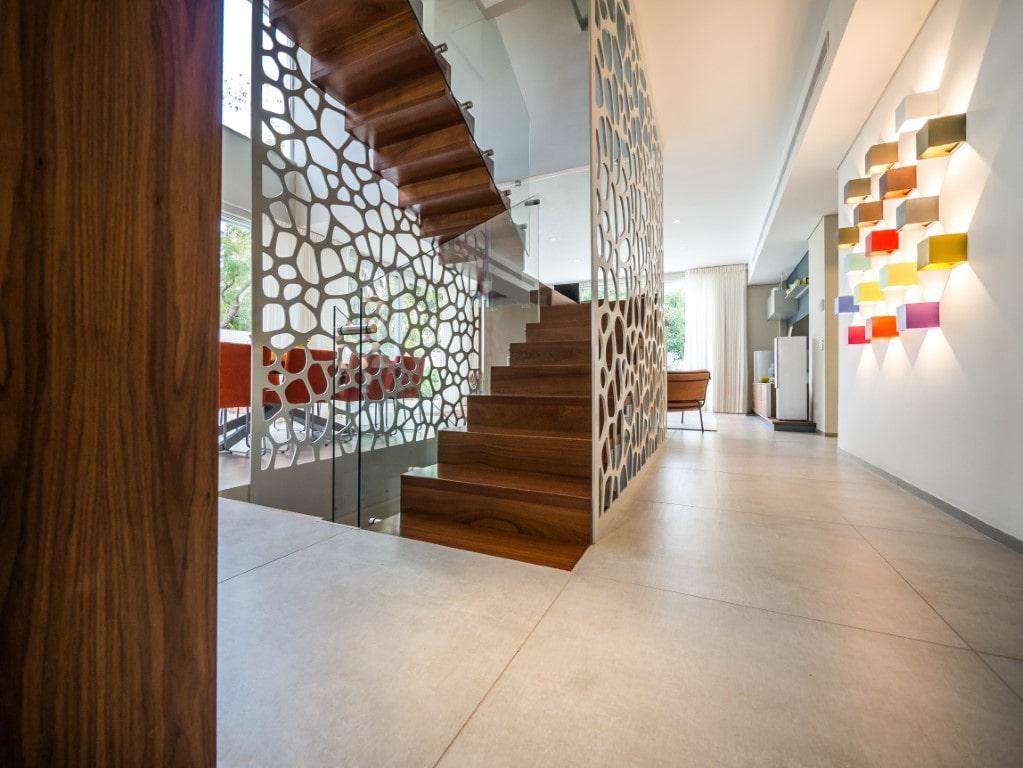 שני גרמי מדרגות עץ מרחפות בין שתי מחיצות דקורטיביות בין פינת האוכל והמסדרון המקושט נורות צבעוניות