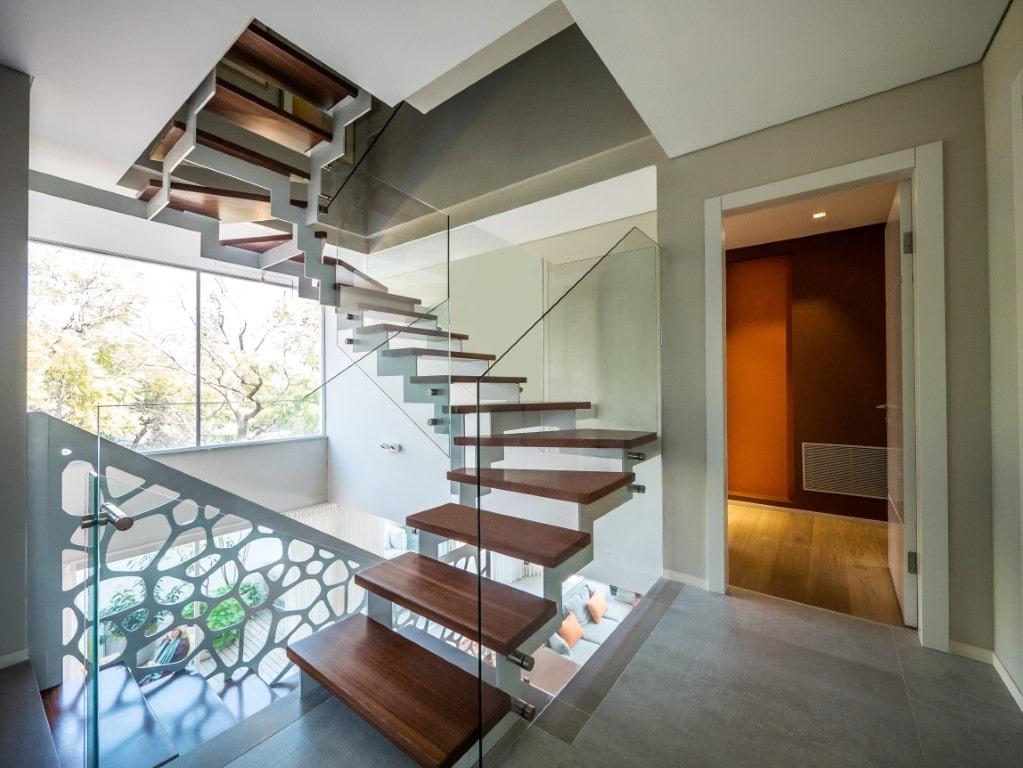 3 גרמי מדרגות מרחפות מעץ בליווי מעקה זכוכית מתפתלים ועולים אל הקומה השניה