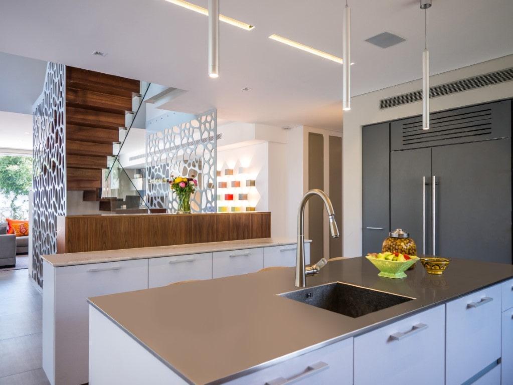 מבט מהמטבח על גרם מדרגות עץ עם מעקה זכוכית ומחיצות דקור לבנות