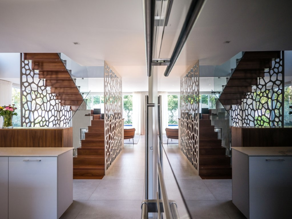 מדרגות עץ ספלי מרחפות מוקפות מחיצות דקור לבנות במרכזו של הבית