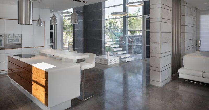 מבט רחב דרך המטבח והסלון אל גרם המדרגות הצפות בלבן