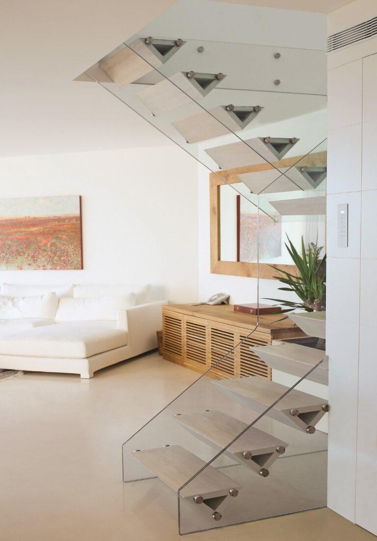 הסלון בלבן מתכתב עם מדרכי עץ האלון המולבן של מדרגות העץ
